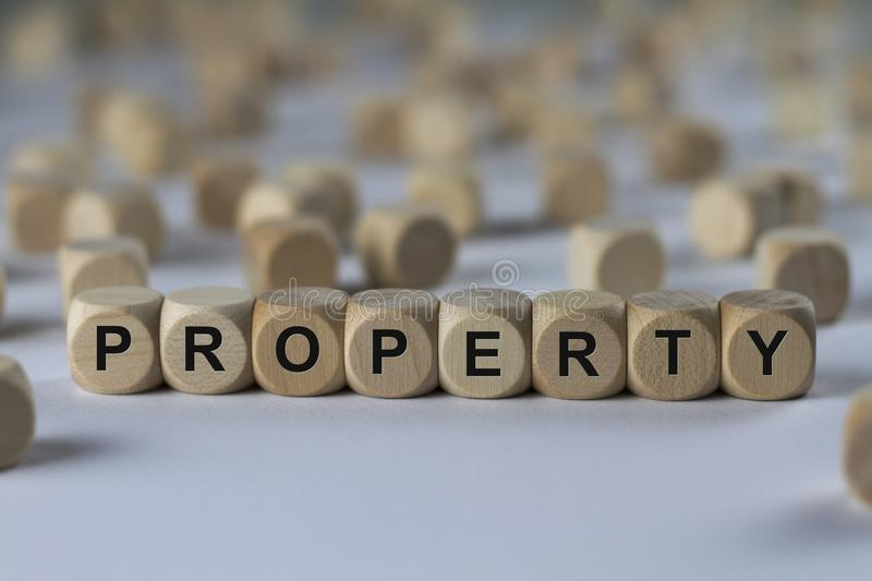 Property - cube with letters, sign with wooden cubes stock image