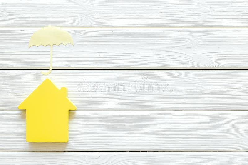 Property insurance concept with house and umbrella toys on white wooden background top view mockup. New house purchase. Property insurance concept with house and royalty free stock images