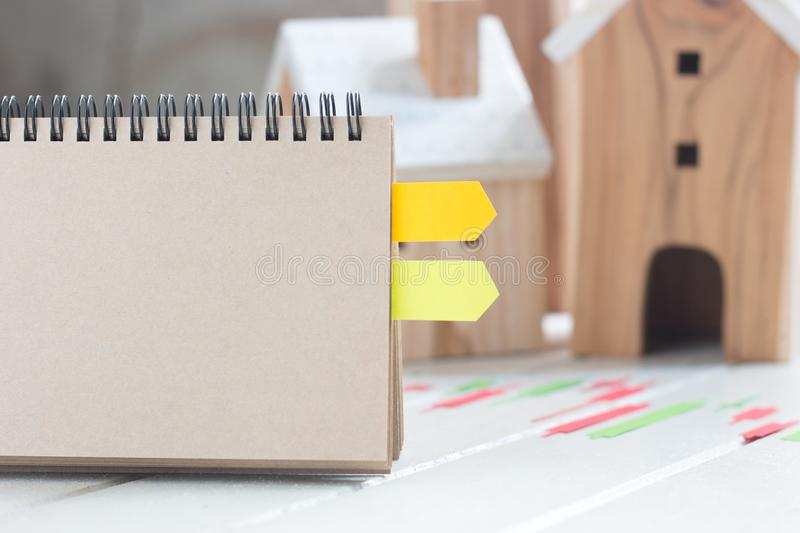 Property investment, Blank paper notebook with Candlestick chart make from color paper Green and red, Miniature house model. Background, financial concept royalty free stock photo
