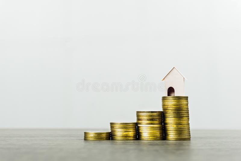 Property investment concept. Savings money for buy new house. Home loan, mortgage. A small house model on stack of coins on wooden. Table against white stock photo