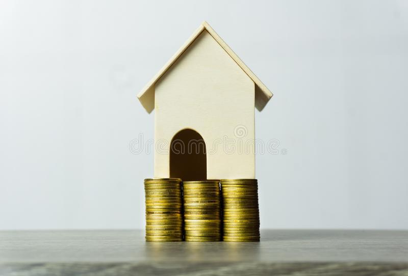 Property investment concept. Savings money for buy new house. Home loan, mortgage. A small house model on stack of coins on wooden. Table against white royalty free stock photo