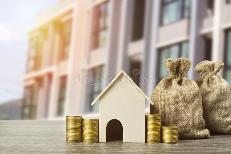 Property investment concept. A small house model with stack of coins and money bag on table. Depicts using real estate turns into stock photo