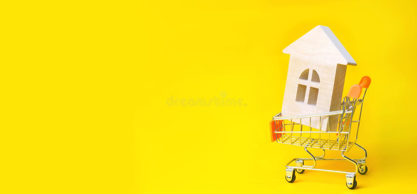 Property investment and house mortgage financial concept. buying, renting and selling apartments. real estate. Wooden house in a S. Upermarket trolley. credit stock photography