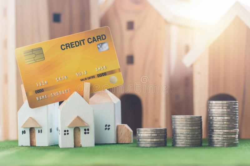 Property investment, Miniature house model with credit card and money coin stack on Simulation grass stock image