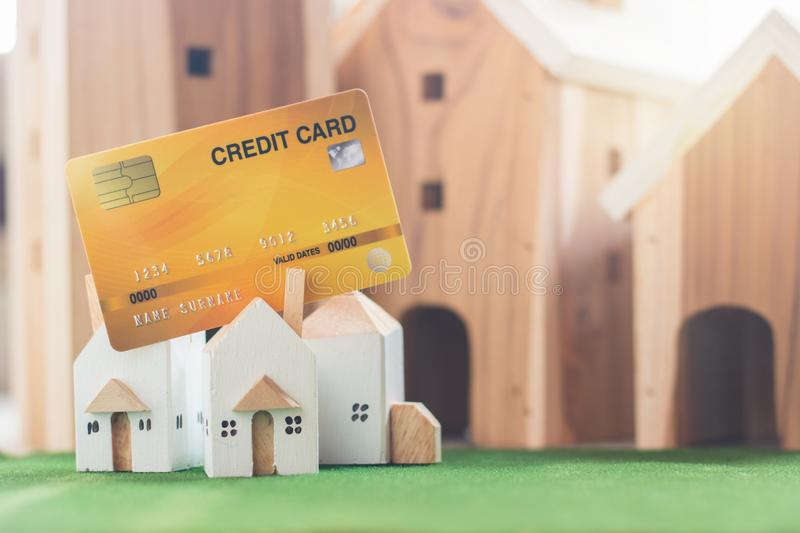Property investment, Miniature house model with credit card on Simulation grass. Wooden house in the background, financial concept stock images
