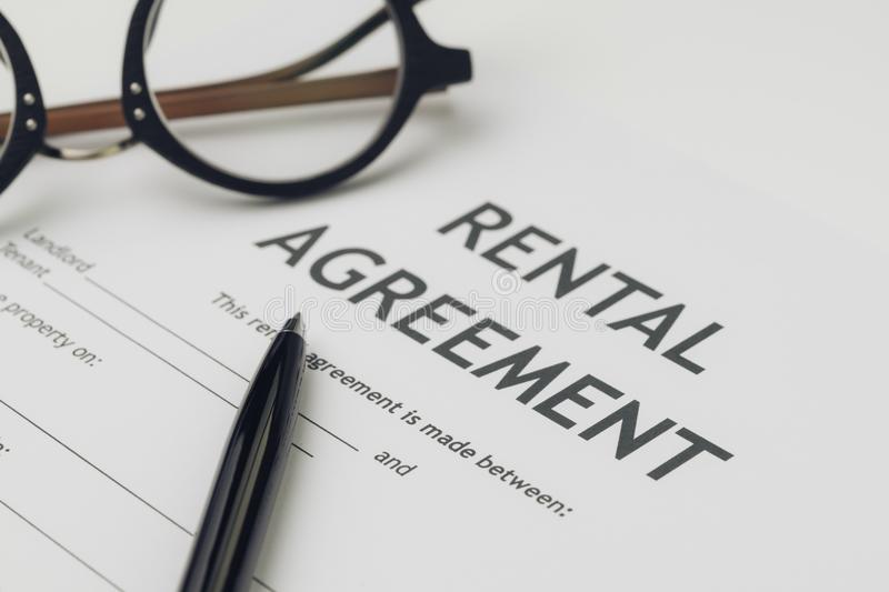 Property or real estate, house and home concept, pen and eyeglasses on rental agreement printed document, ready to sign contract.  stock image