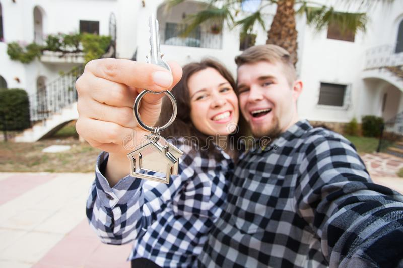 Property, real estate and rent concept - Happy smiling young couple showing a keys of their new house royalty free stock image