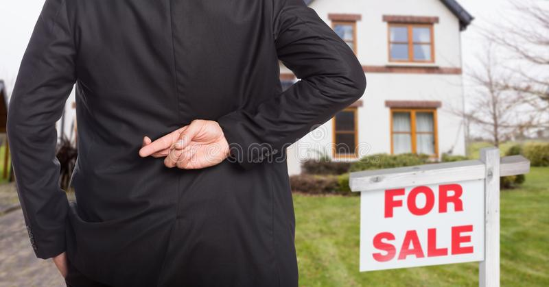 property seller with his fingers crossed stock images