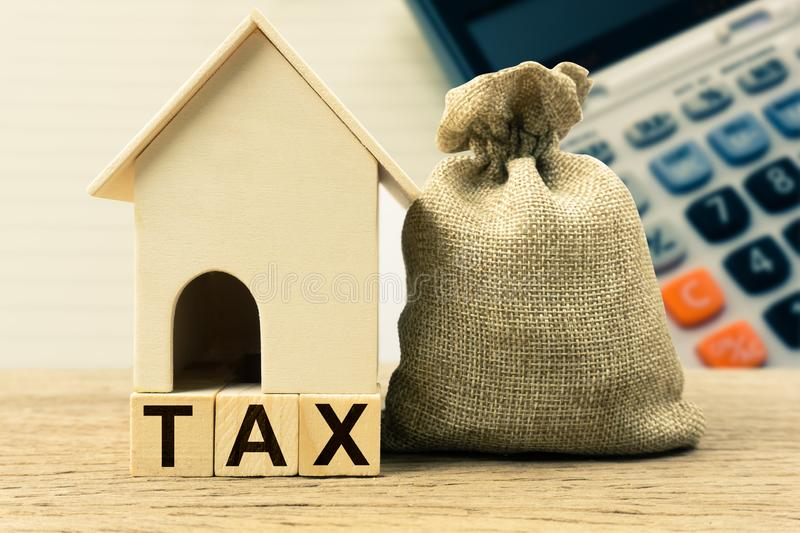 A property tax or millage rate concepts. Small house model with taxes and money bag on table. Depicts the tax is levied by the governing authority of the stock photo