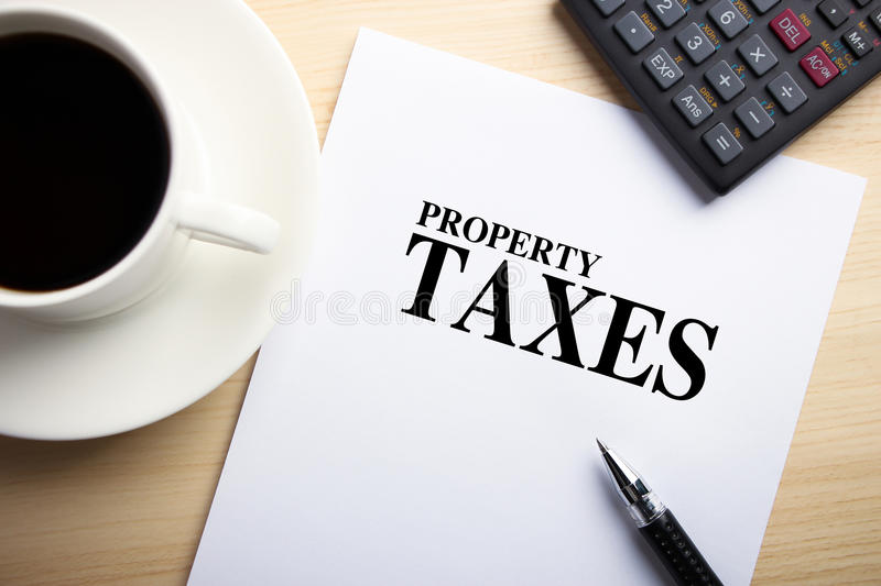 Property Taxes. Text Property Taxes is on the white paper with coffee, calculator and ball pen aside royalty free stock photos