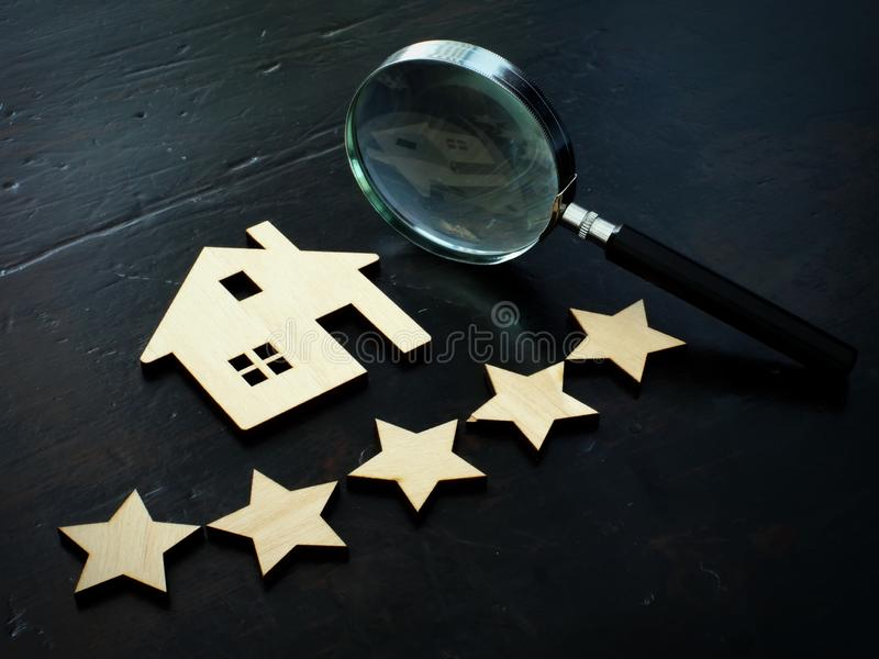 Property valuation and home appraisal. Model of house and five stars stock photography