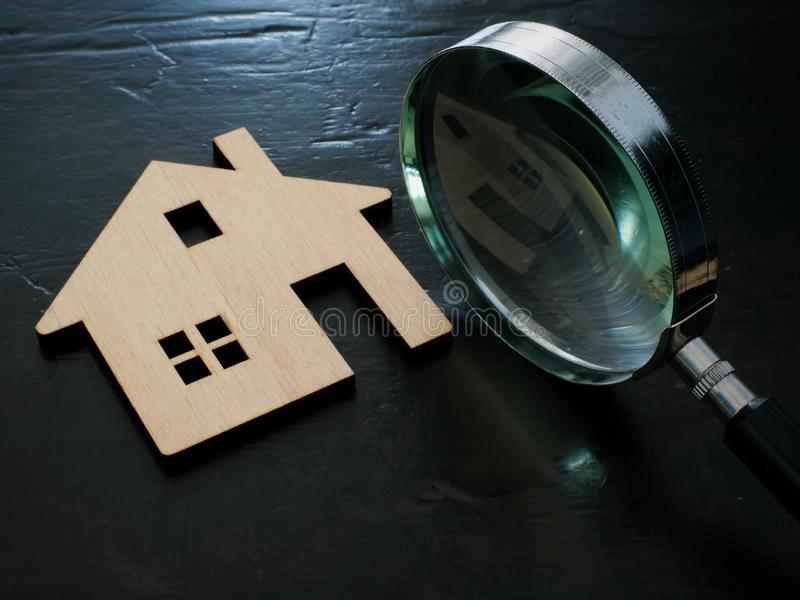 Property valuation. Magnifying glass and wooden model of home stock photography