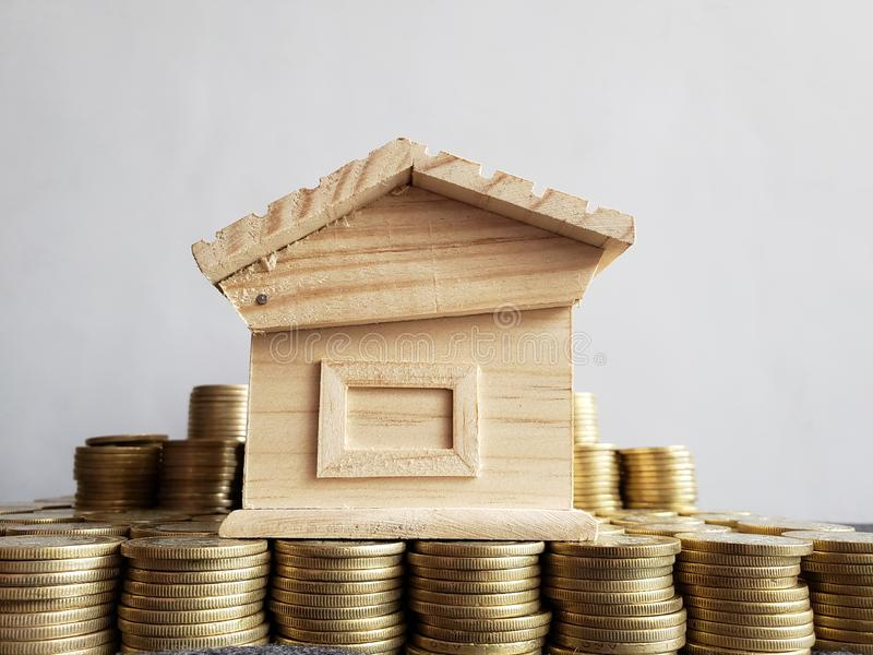 property value, stacked coins and a wooden figure of a house stock photography