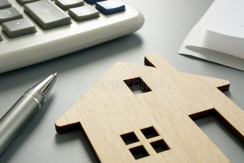 Property worth concept. Wooden model and calculator stock image