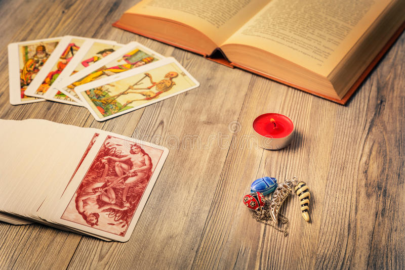 The prophecy. Composition of esoteric objects, candle, Tarots and book used for healing and fortune-telling, vintage style royalty free stock images
