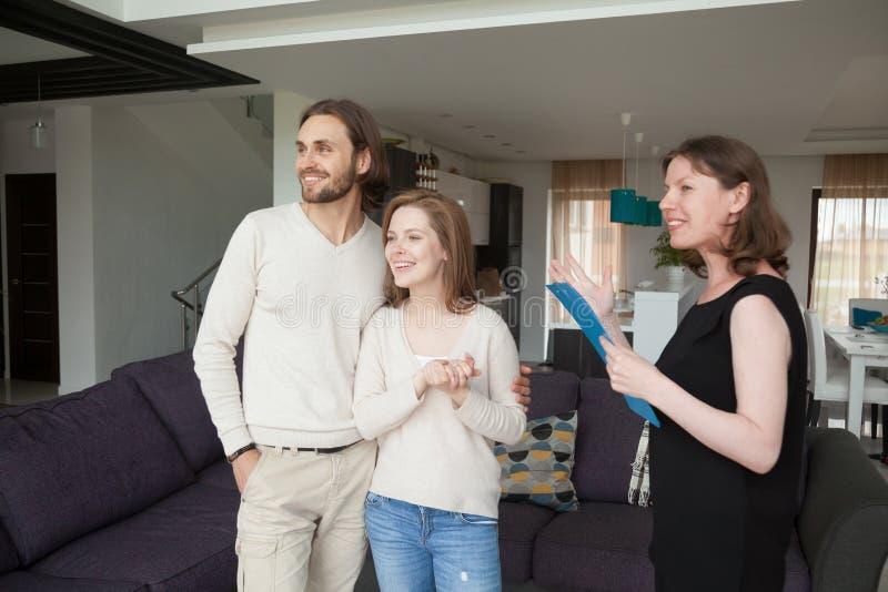 Propiedad de la demostración del agente inmobiliario en venta a la pareja de matrimonios joven imágenes de archivo libres de regalías
