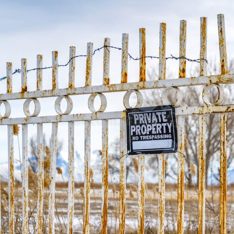 Propiedad privada cuadrada clara ninguna muestra de violación en una puerta oxidada con la cadena y el candado fotos de archivo