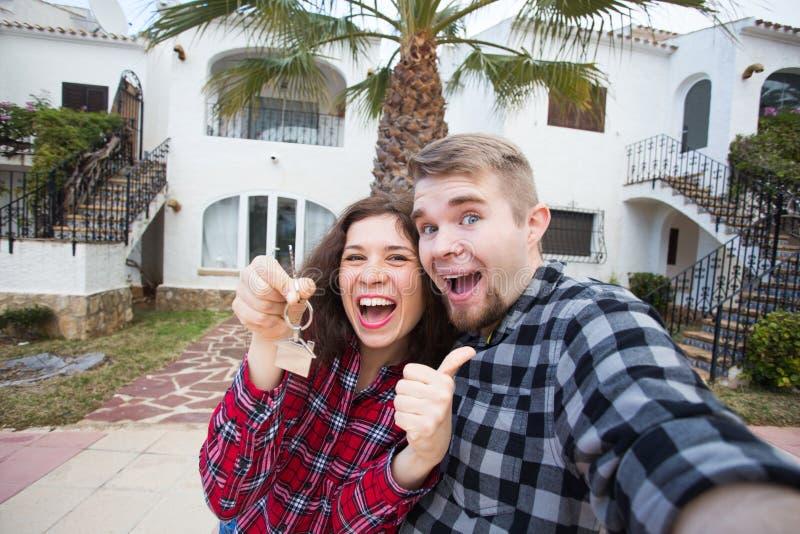 Propiedad, propiedades inmobiliarias y concepto del alquiler - el mostrar joven divertido feliz de los pares llaves de su nueva c fotos de archivo