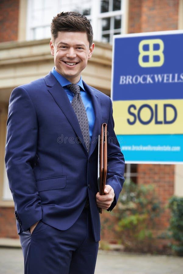 Propiedad residencial del exterior derecho masculino del agente inmobiliario con Sig vendidos foto de archivo libre de regalías