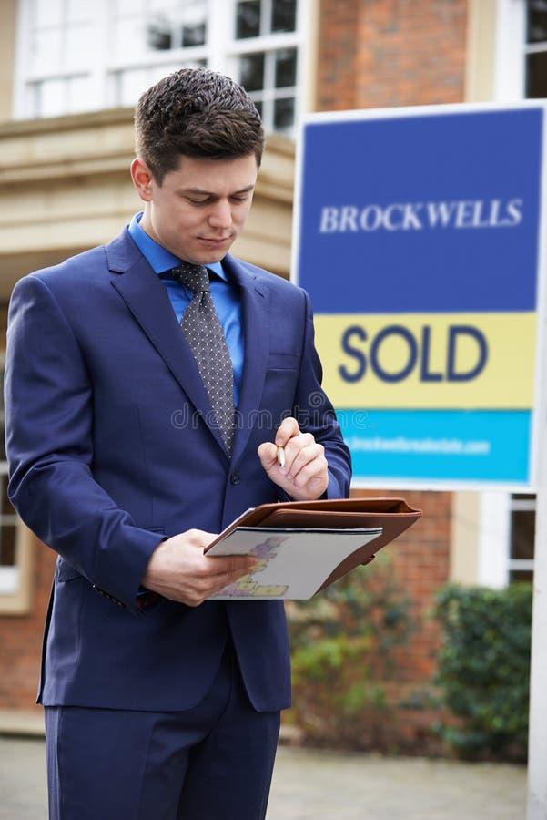 Propiedad residencial del exterior derecho masculino del agente inmobiliario con Sig vendidos foto de archivo