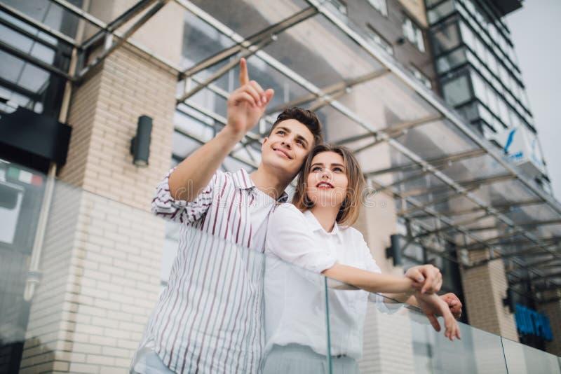 Propiedades inmobiliarias y concepto de familia Los pares jovenes señalaron el lado en frente de la nueva construcción moderna gr imagenes de archivo