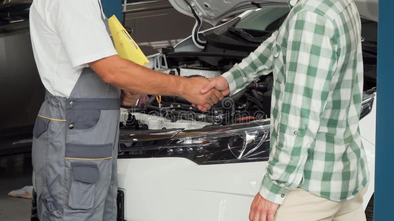 Propietario de coche que sacude las manos con el mecánico de automóviles en la gasolinera fotografía de archivo libre de regalías