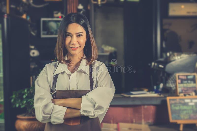 Propietario de negocio acertado del barista asiático de la mujer pequeño que se coloca adentro fotos de archivo