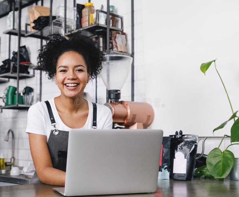 Propietario de negocio feliz que se coloca en el contador imagen de archivo libre de regalías