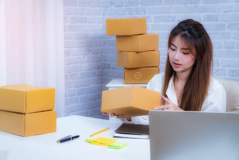 Propietario de negocio de las mujeres jovenes que trabaja en casa la oficina que empaqueta en fondo empresario en línea de la PME fotografía de archivo