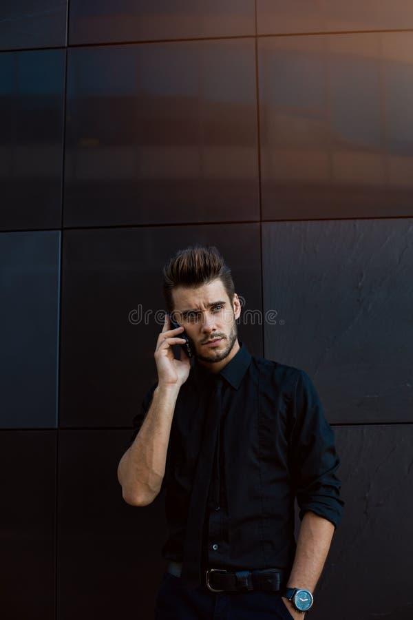 Propietario de negocio orgulloso de sexo masculino que llama vía el teléfono móvil Hombres brutales que tienen conversación del t fotografía de archivo