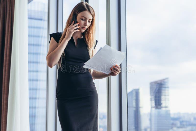 Propietario de negocio de sexo femenino joven elegante que lleva a cabo los documentos que hablan en el teléfono móvil que discut fotos de archivo