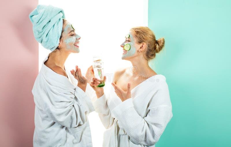 Propio salón del balneario en casa Concepto del cuidado de piel usando la máscara y los pepinos blancos en la cara Dos hermanas f imagen de archivo