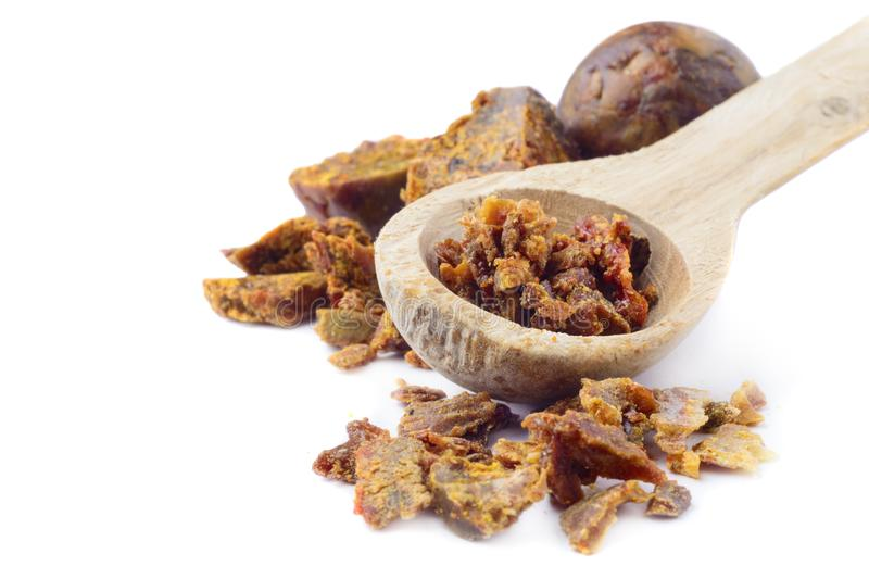 Propolis granules in a wooden spoon are isolated on a white background. Bee glue. Bee products. Apitherapy. Apiculture. Propolis granules in a wooden spoon are royalty free stock images