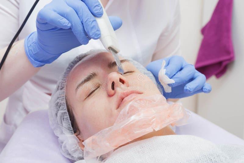 Proporcionan la muchacha un servicio de limpieza de la piel del ultrasonido en el salón de belleza fotos de archivo