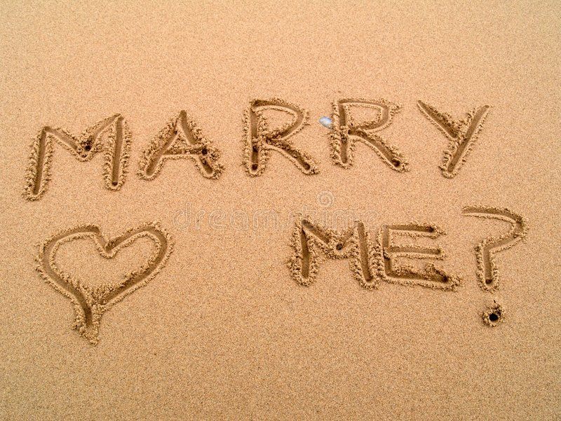 Proposal. A proposal of marriage and love written in sand on the beach with a drawn heart
