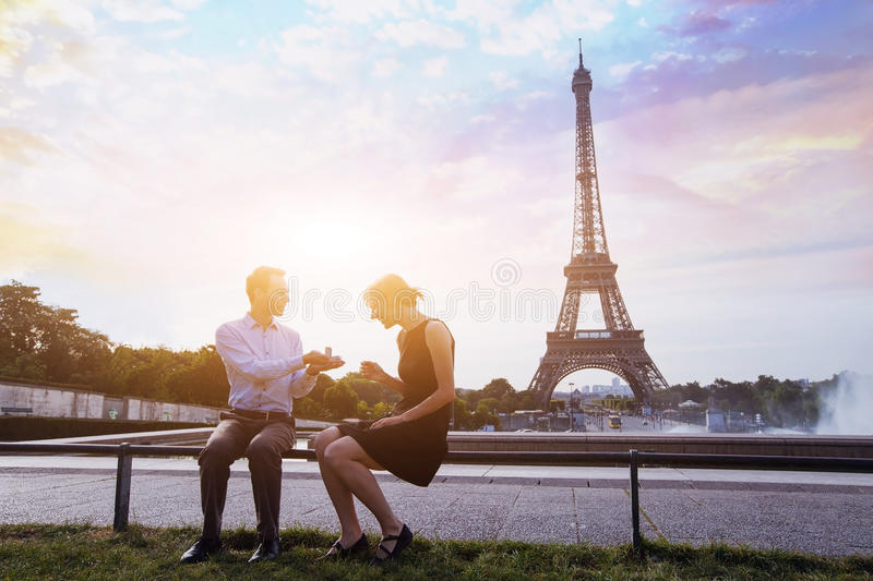 Proposal at Eiffel Tower. Marry me, proposal at Eiffel Tower in Paris, beautiful silhouettes of young caucasian couple stock images