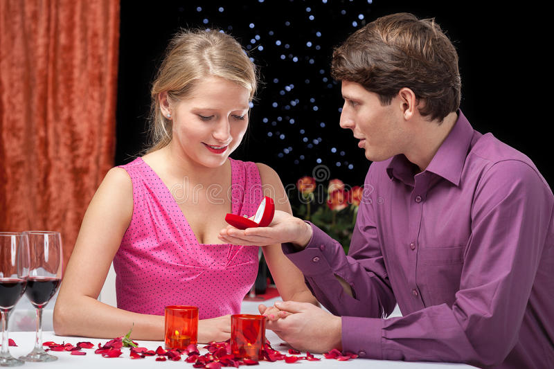 Proposal on Valentine's Day. Elegant men proposing to his girlfriend in exclusive restaurant stock photo