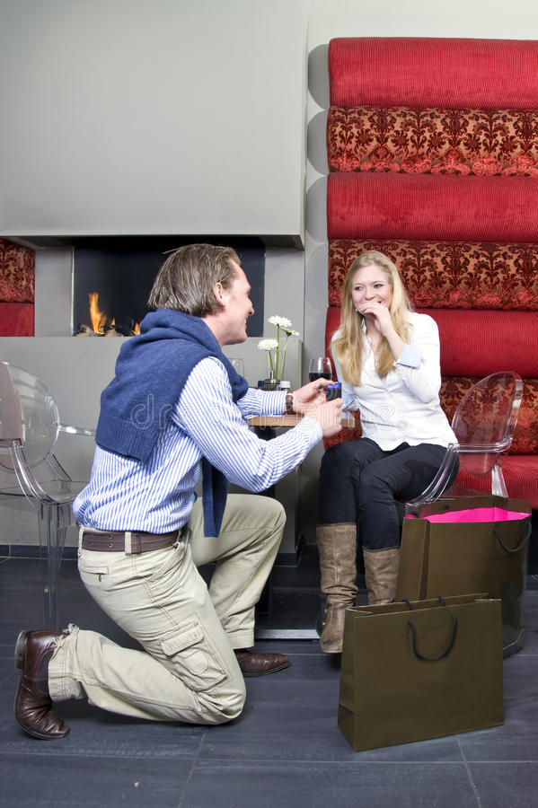 Proposing. A man proposing to a woman in front of a restaurant fireplace royalty free stock image