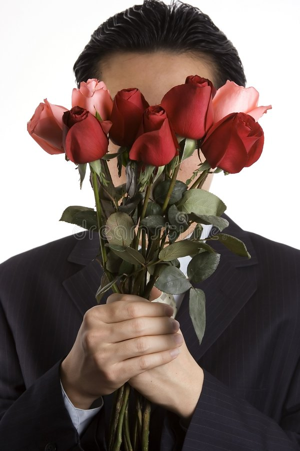 Proposing. A man with business suite holding roses proposing stock image