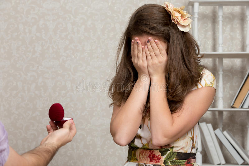 Proposing. Girl covers her face with hands after being proposed to royalty free stock image