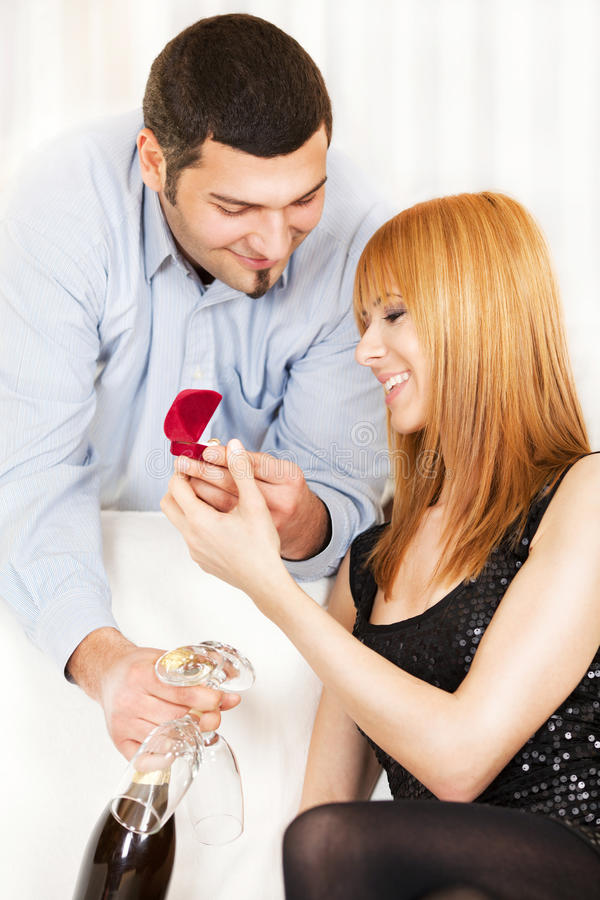 Proposing marriage. Young men proposing marriage to beautiful girl at home ambient stock photos