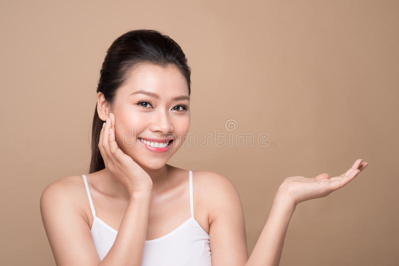 Proposing a product. Beautiful spa woman showing empty copy space on the open hand palm royalty free stock images