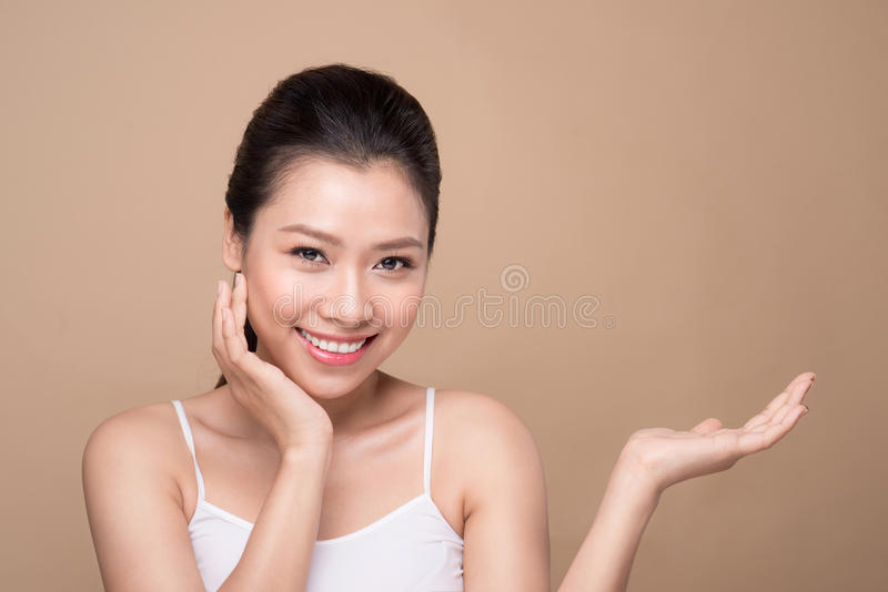 Proposing a product. Beautiful spa woman showing empty copy space on the open hand palm royalty free stock photography
