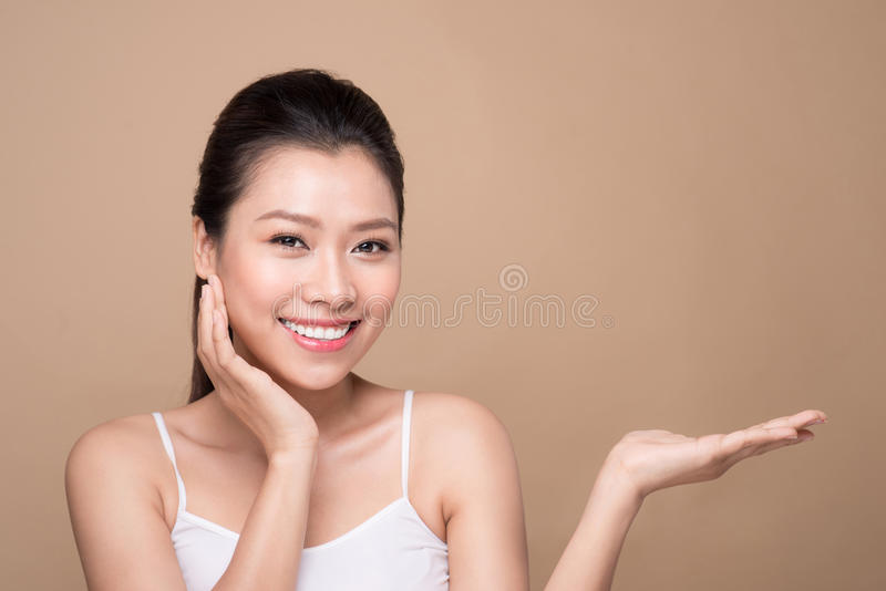 Proposing a product. Beautiful spa woman showing empty copy space on the open hand palm stock images