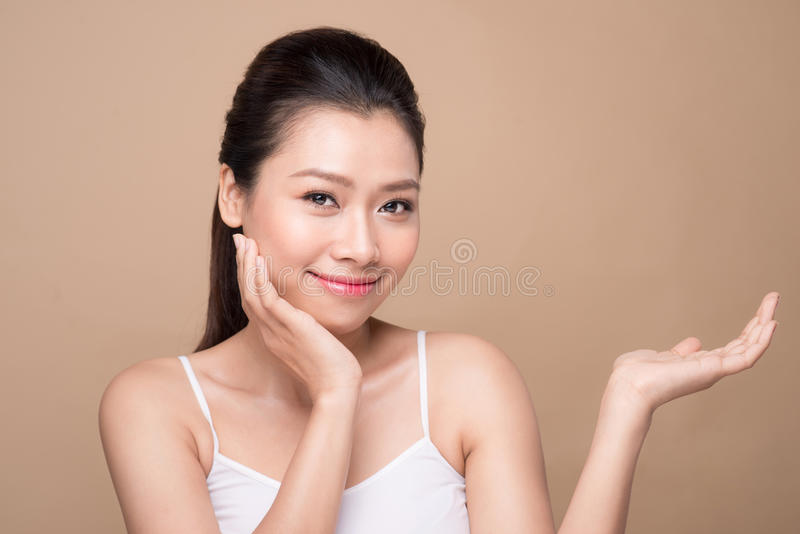 Proposing a product. Beautiful spa woman showing empty copy space on the open hand palm royalty free stock photos