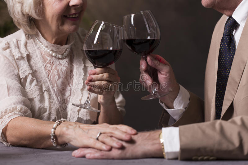 Proposing a toast. Cropped picture of an old couple proposing a toast and holding hands royalty free stock image