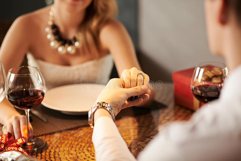 Proposing a toast. Man holding hand of his wife and proposing a toast to her stock photos