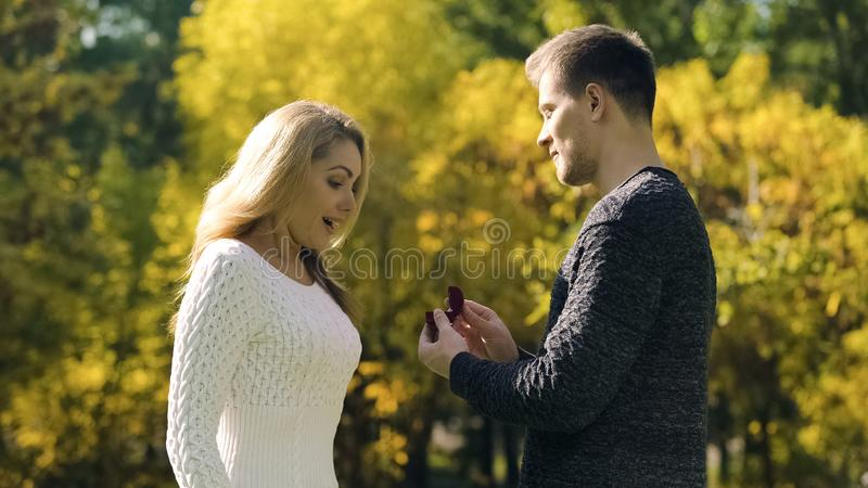 Proposition de surprise en parc de chute, couple enthousiaste, engagement avec l'anneau, bonheur images stock