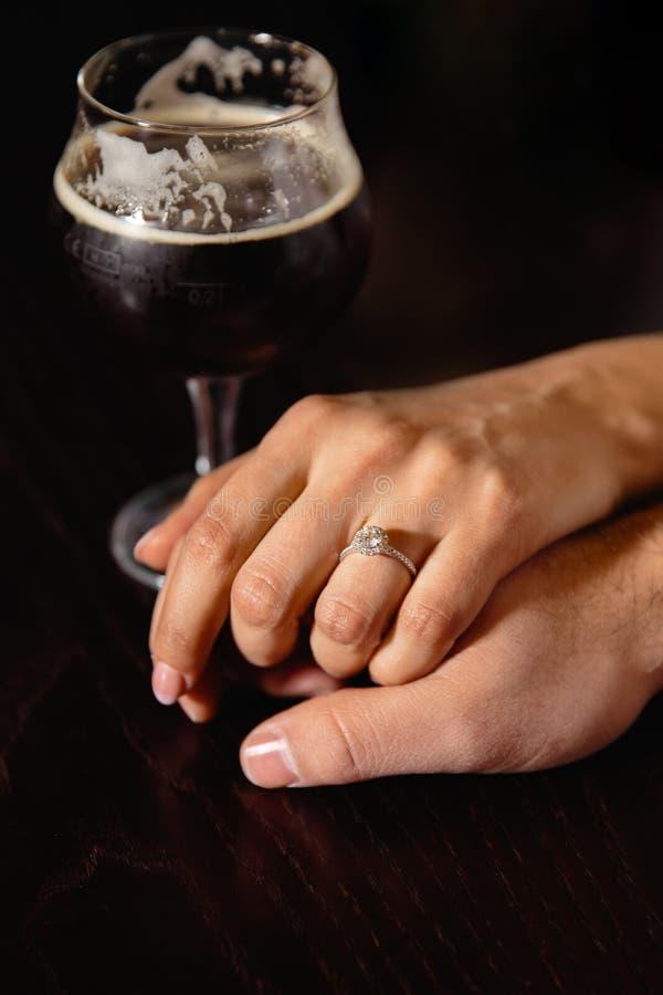 Proposition de vie réelle : Couplez tenir des mains dans un bar avec un verre de bière à leur côté photo stock