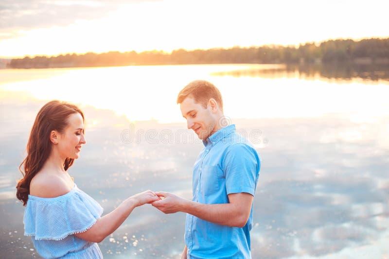 Proposta di matrimonio sul tramonto il giovane presenta una proposta del fidanzamento alla sua amica sulla spiaggia immagini stock